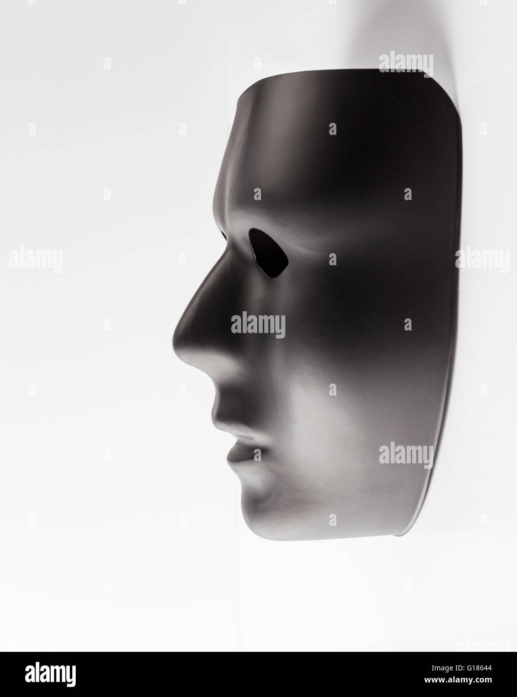 Black mask profile emerging from white background. Hidden identity concept. - Stock Image