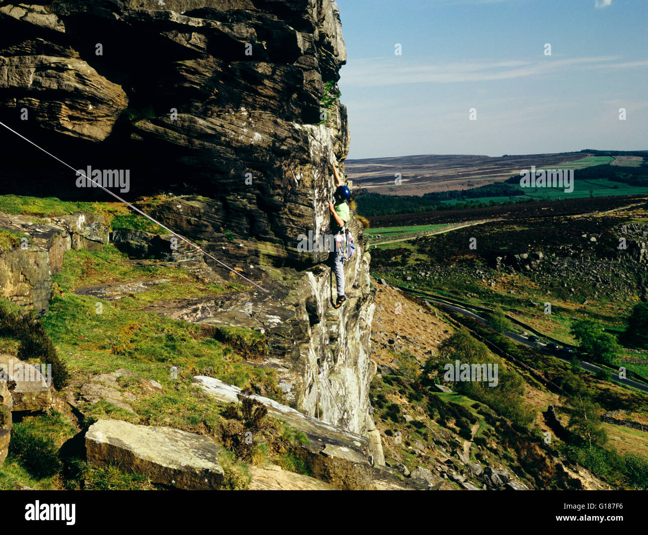 Man climbing Peapod a severe challenging climb on Curbar Edge Peak District Derbyshire England UK  roped to steep - Stock Image
