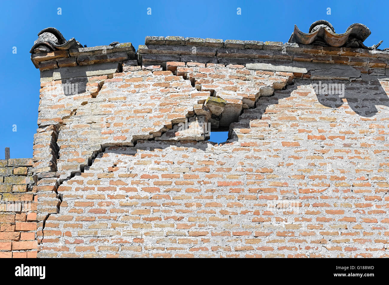 Wall damaged and broken. Building in ruins. Facade dilapidated. Abstract background. Some tiles at roof. - Stock Image