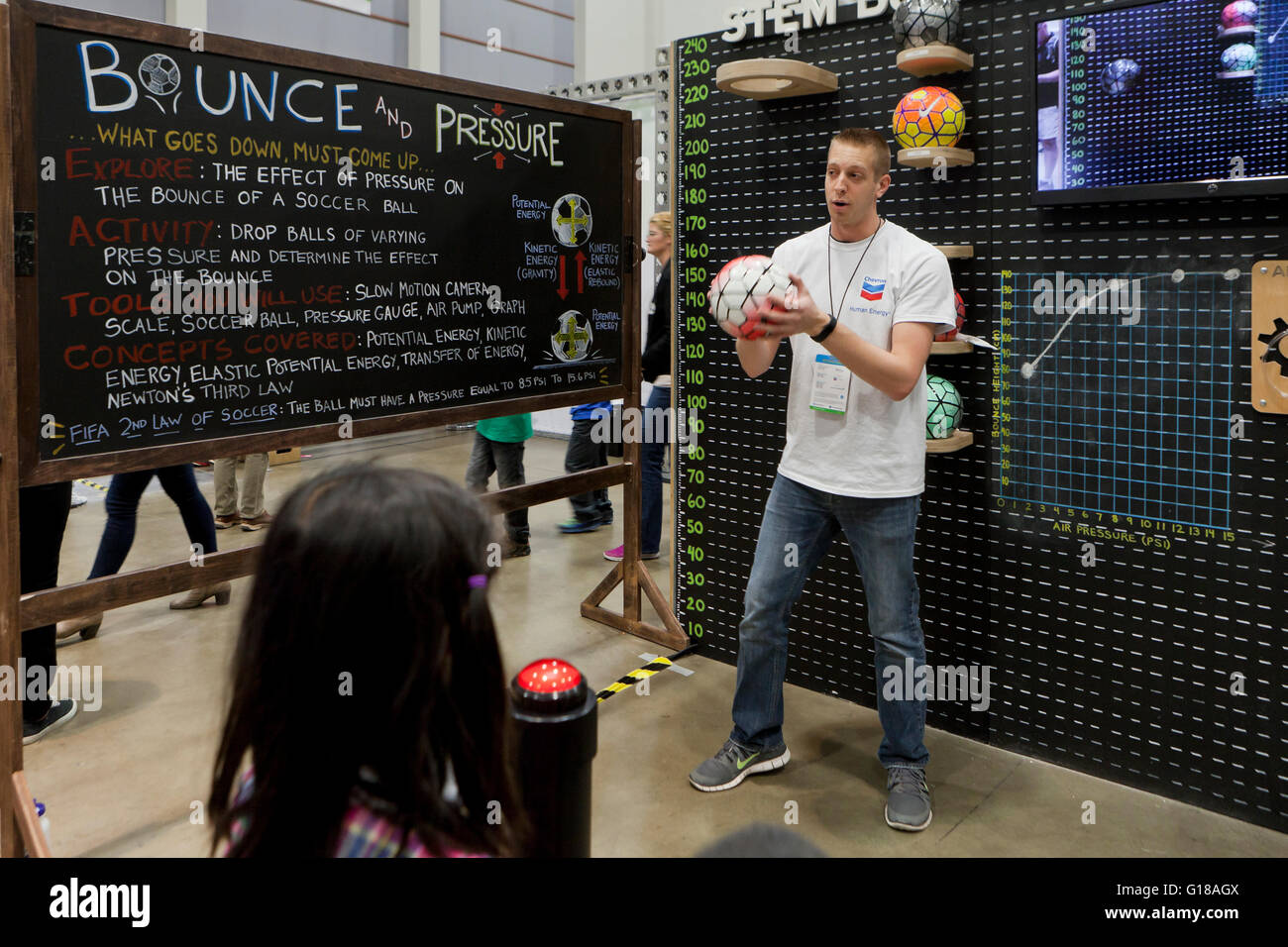 A scientist demonstrating potential energy and kinetic energy with soccer ball bounce at science fair - USA - Stock Image