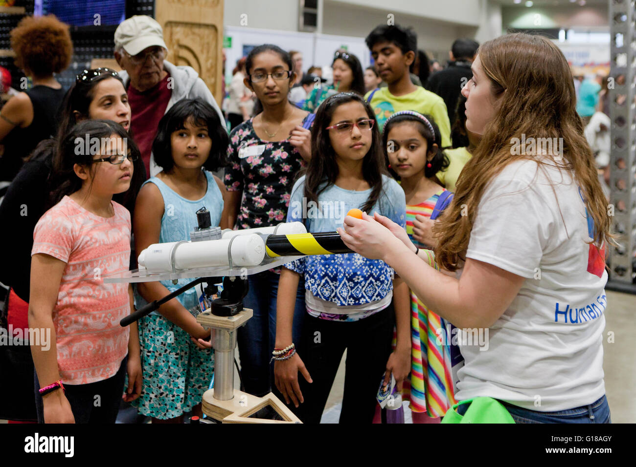 Female students learning physics at science fair - USA - Stock Image