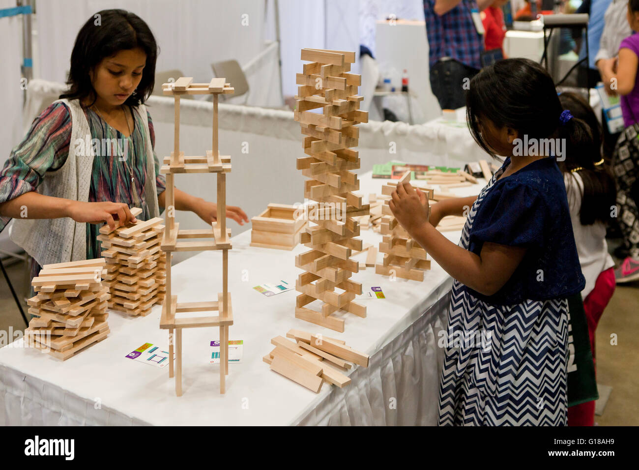 Girls stacking wooden toy blocks at science fair - USA Stock Photo