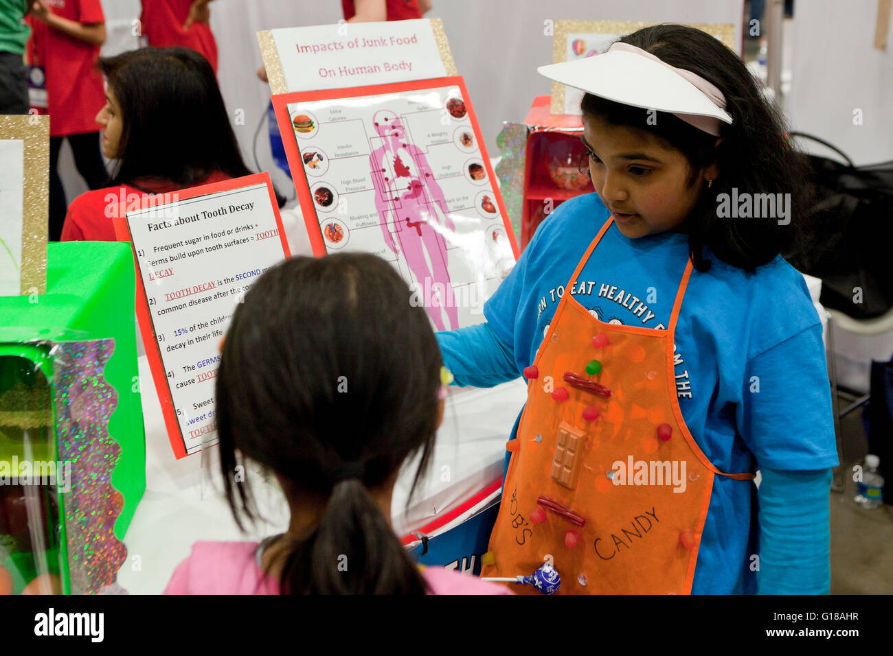 Female students at a food nutrition project booth at science fair - USA - Stock Image