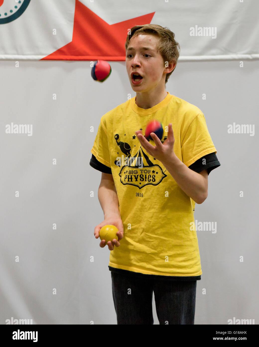 Young man juggling 3 balls - USA - Stock Image