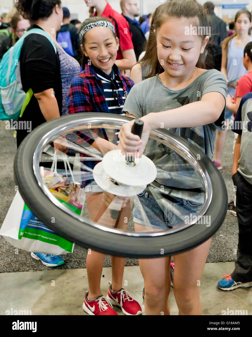 Young girl learning physics of gyroscope with a bicycle wheel at a science fair - USA - Stock Image