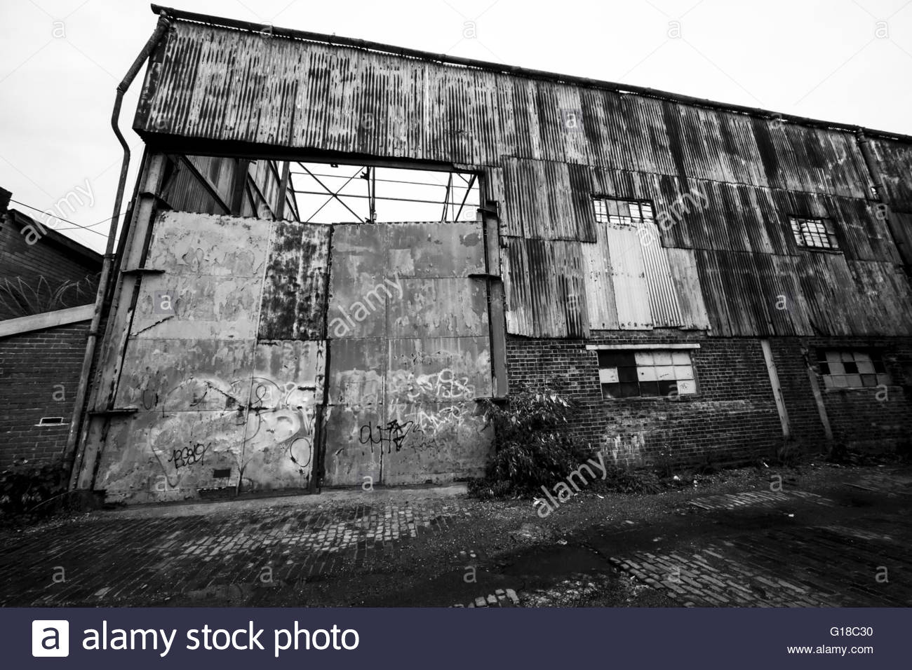Scruffy factory unit on a cobbled back road close to the River Thames - Stock Image