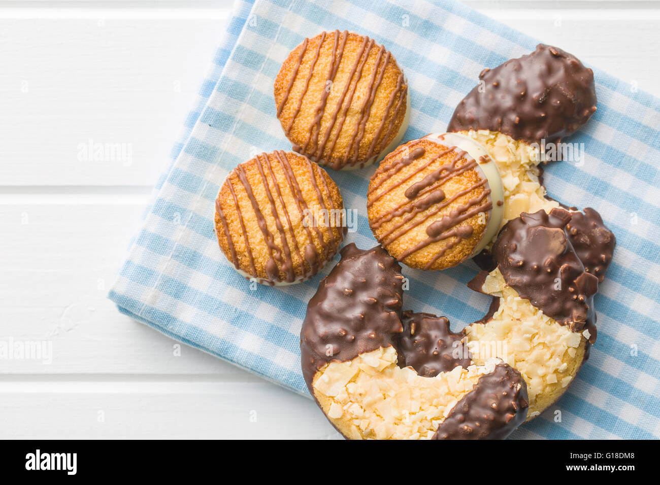 Sweet dessert. Biscuits with chocolate icing on checkered napkin. - Stock Image