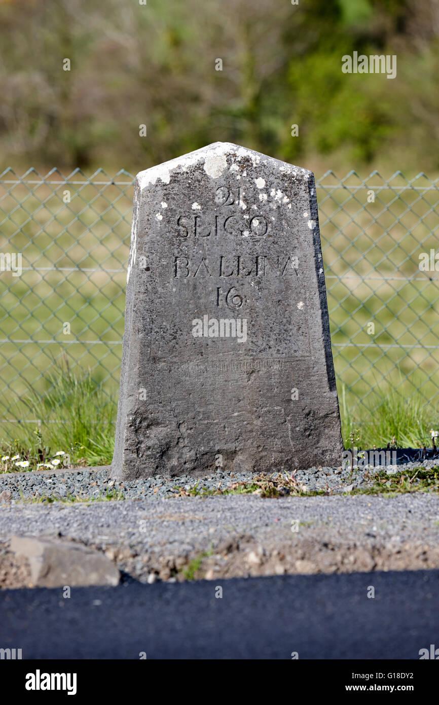 old irish milestone marker by the side of new road Enniscrone county sligo Ireland - Stock Image