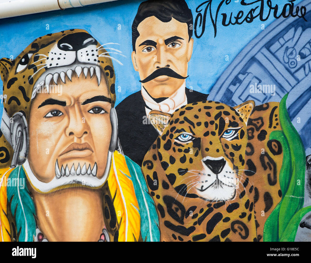 Urban art depicting Mexican Indian with headdress, leopard and modern Mexican man in city of Jalpan de Serra, Querétaro, - Stock Image