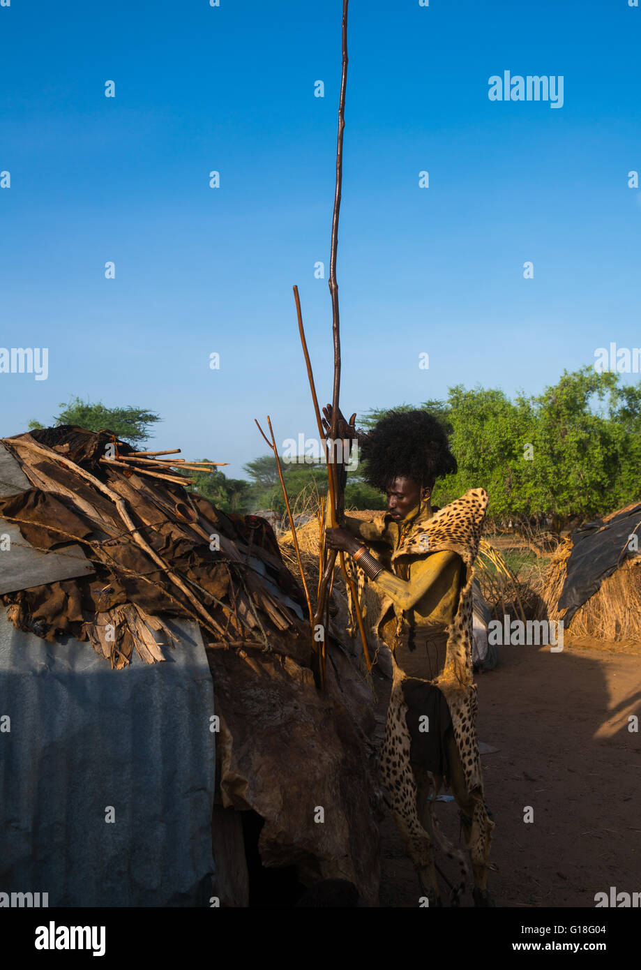 Dassanech man with leopard skin and ostrich feathers headwear during dimi ceremony to celebrate circumcision of - Stock Image