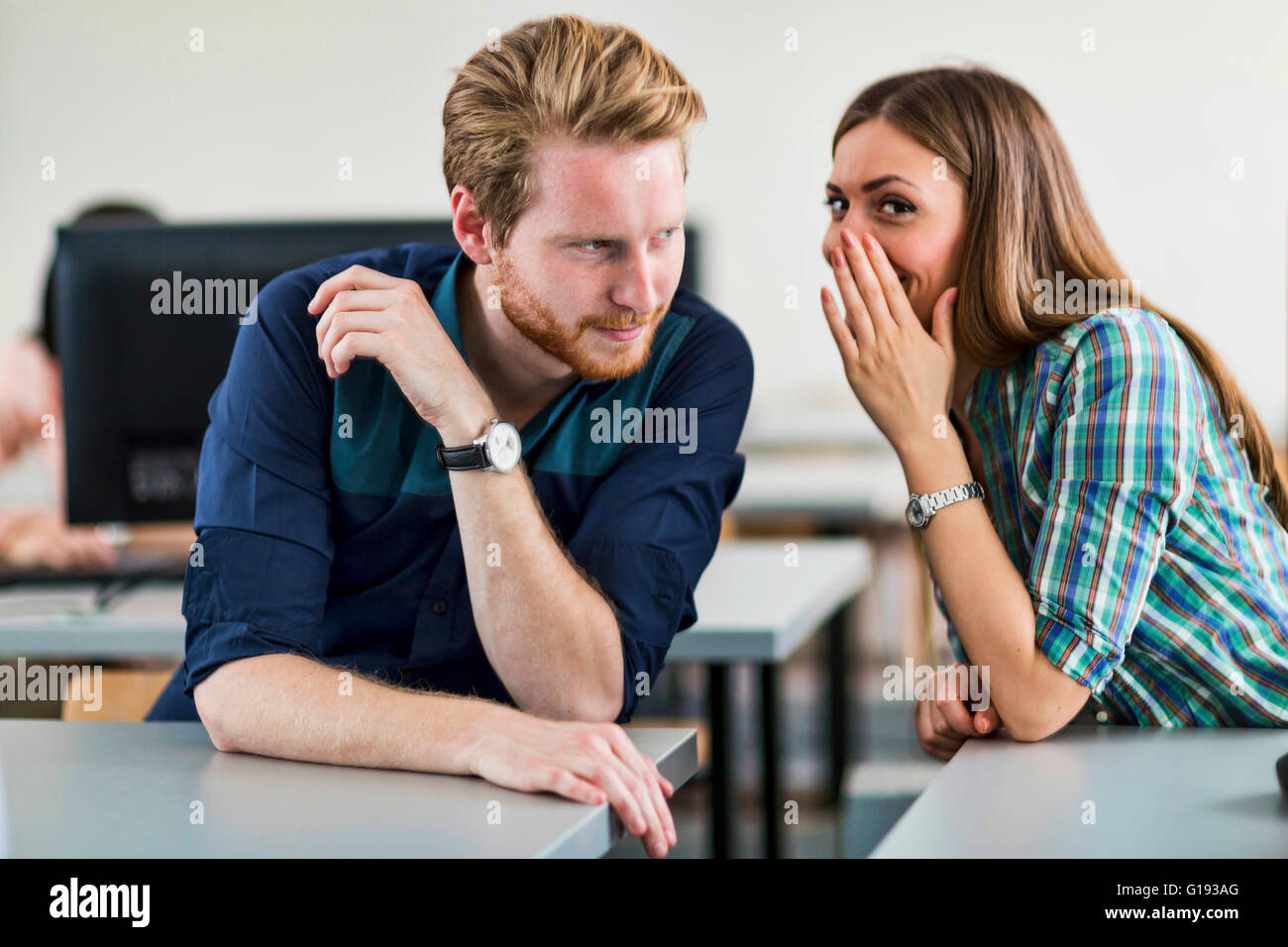 Students cheating by whispering to each other in a classroom - Stock Image
