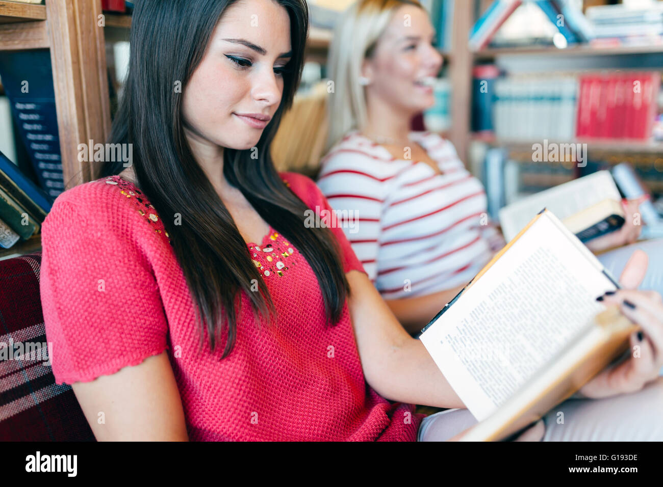 Friends reading books and studying for exam together - Stock Image