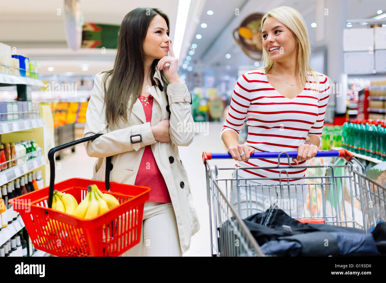 Two beautiful women shopping in supermarket - Stock Image