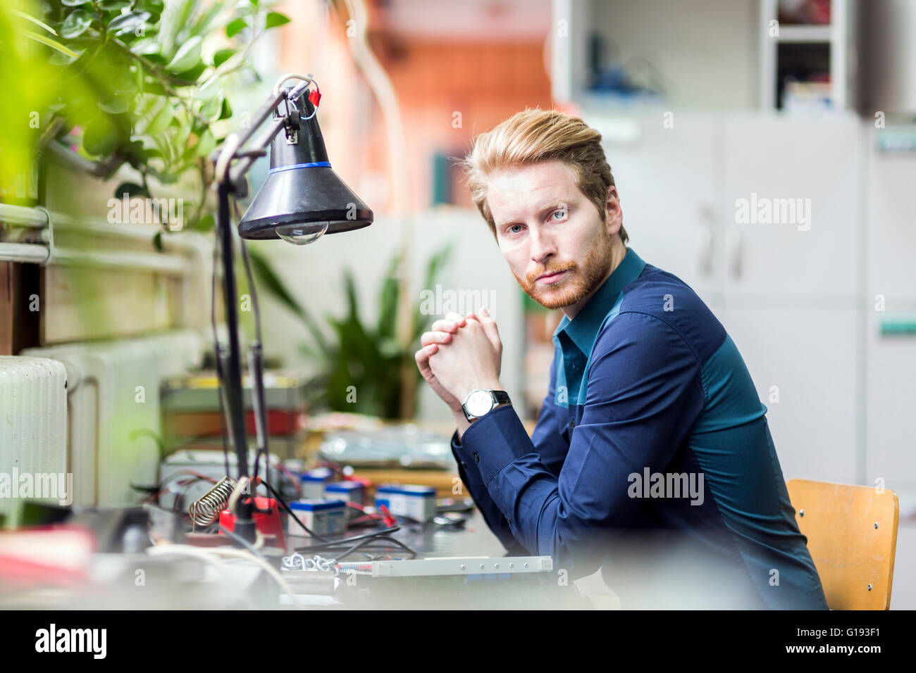 Young handsome man thinking how to solder the circuit board and fix it - Stock Image