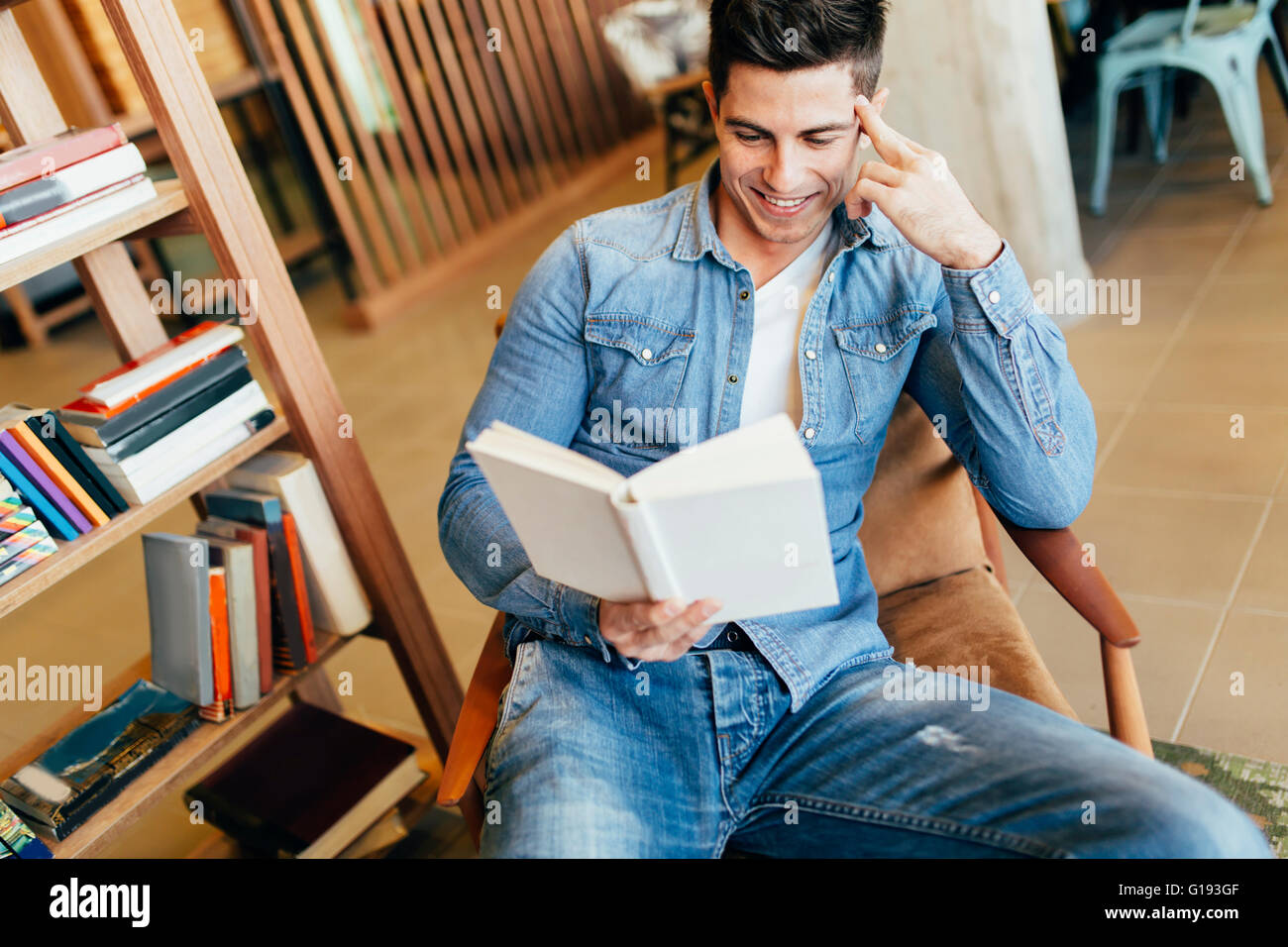 Handsome man studying by reading books and preparing for exam - Stock Image