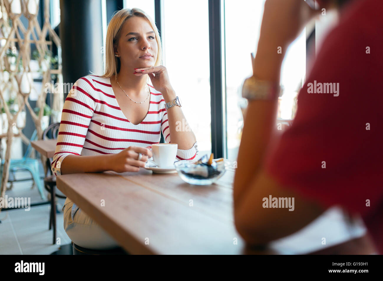 Beautiful women drinking coffee and gossiping in nice restaurant Stock Photo