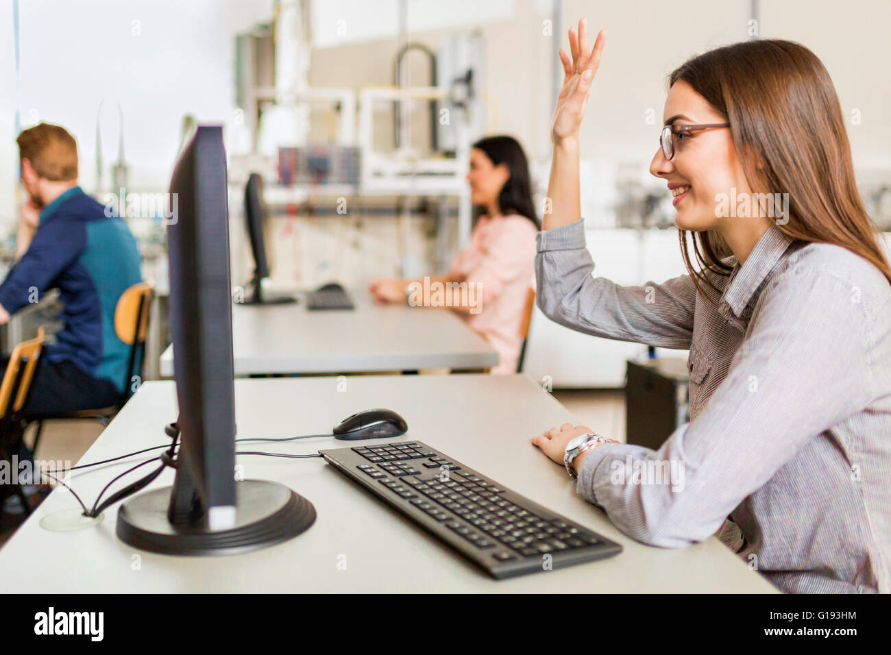 Beautiful young girl raising hand in classroom while sitting at a desk - Stock Image