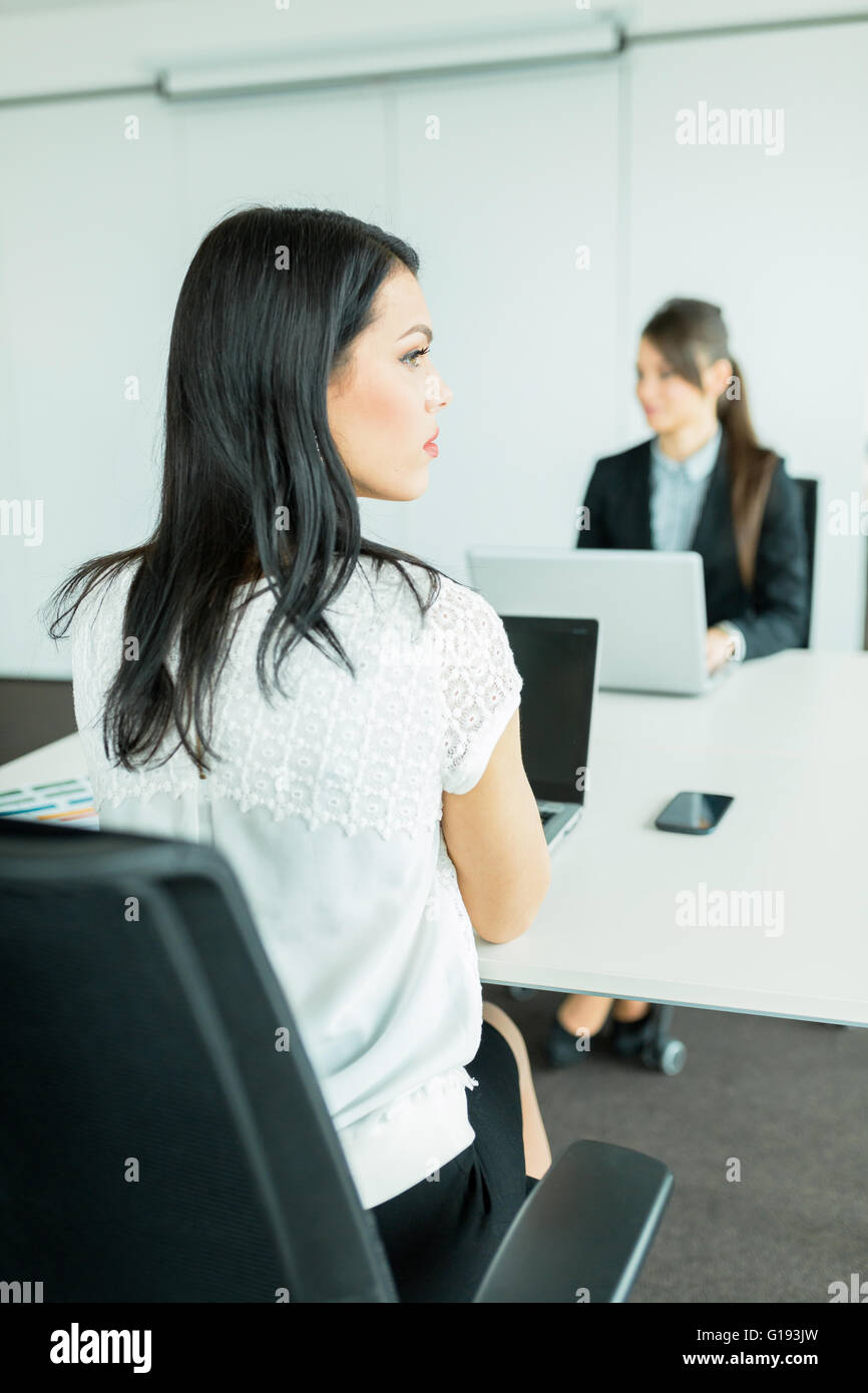 Beautiful young businesswoman looking away from the desk in an office while her colleague works on a laptop - Stock Image