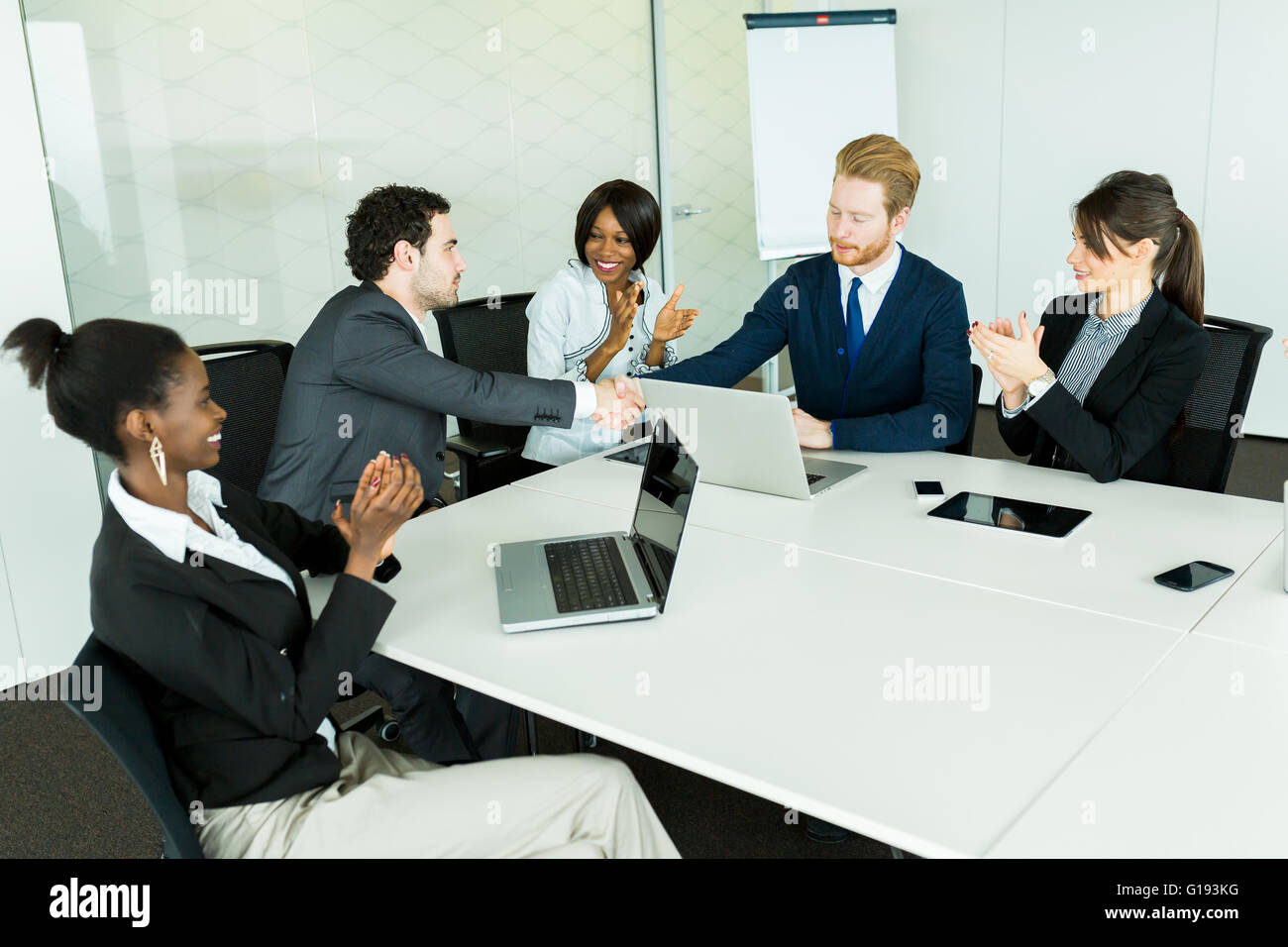 Business deal made between two businessmen in a neat office environment followed by a round of applause Stock Photo