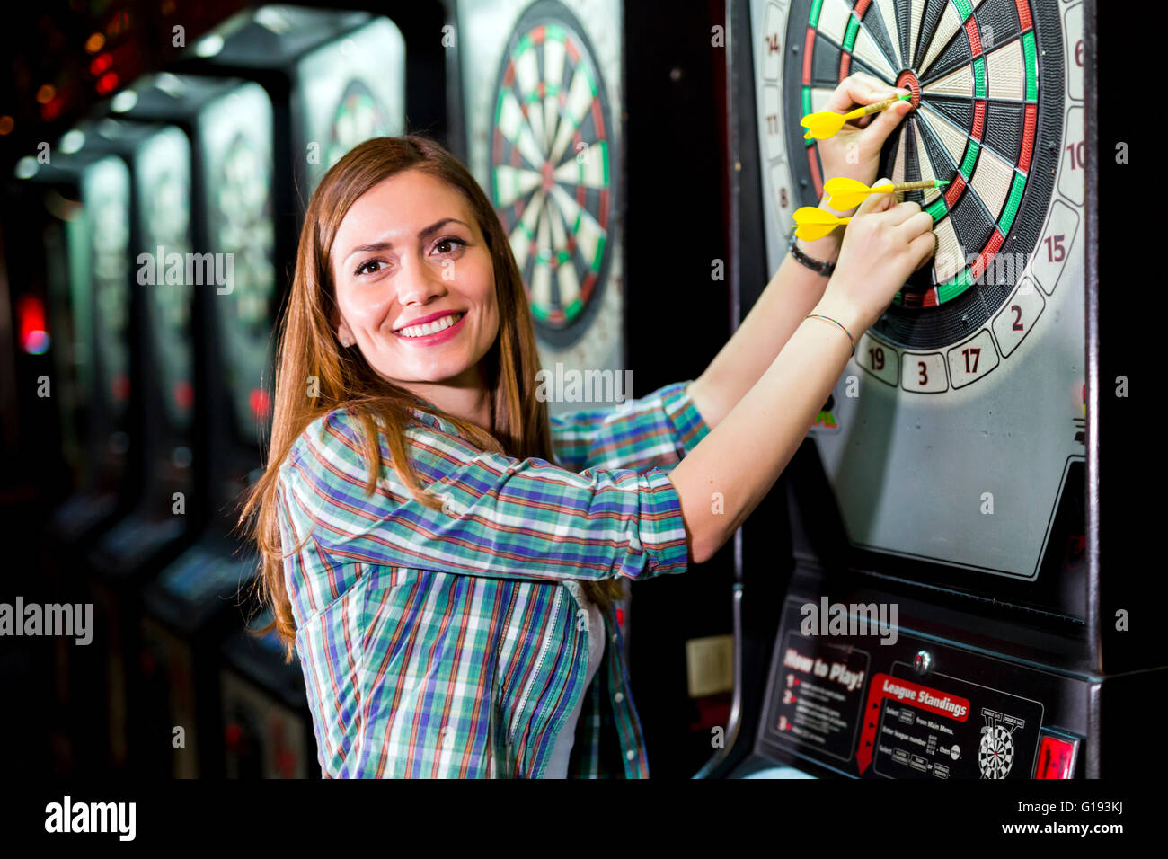Young beautiful woman playing darts in a club and smiling - Stock Image