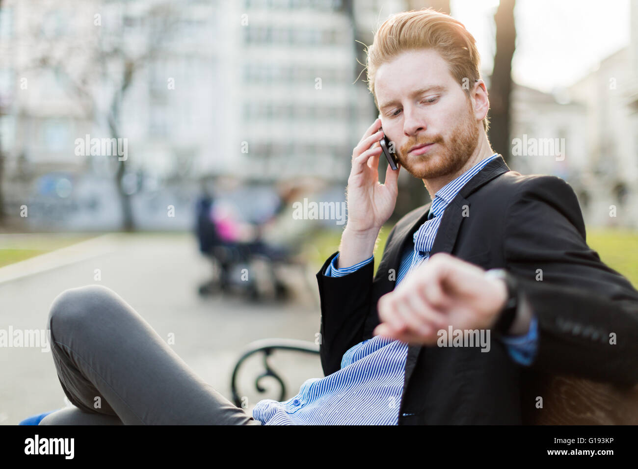 Businessman looking at his wrist watch on a sunny day in a city park - Stock Image