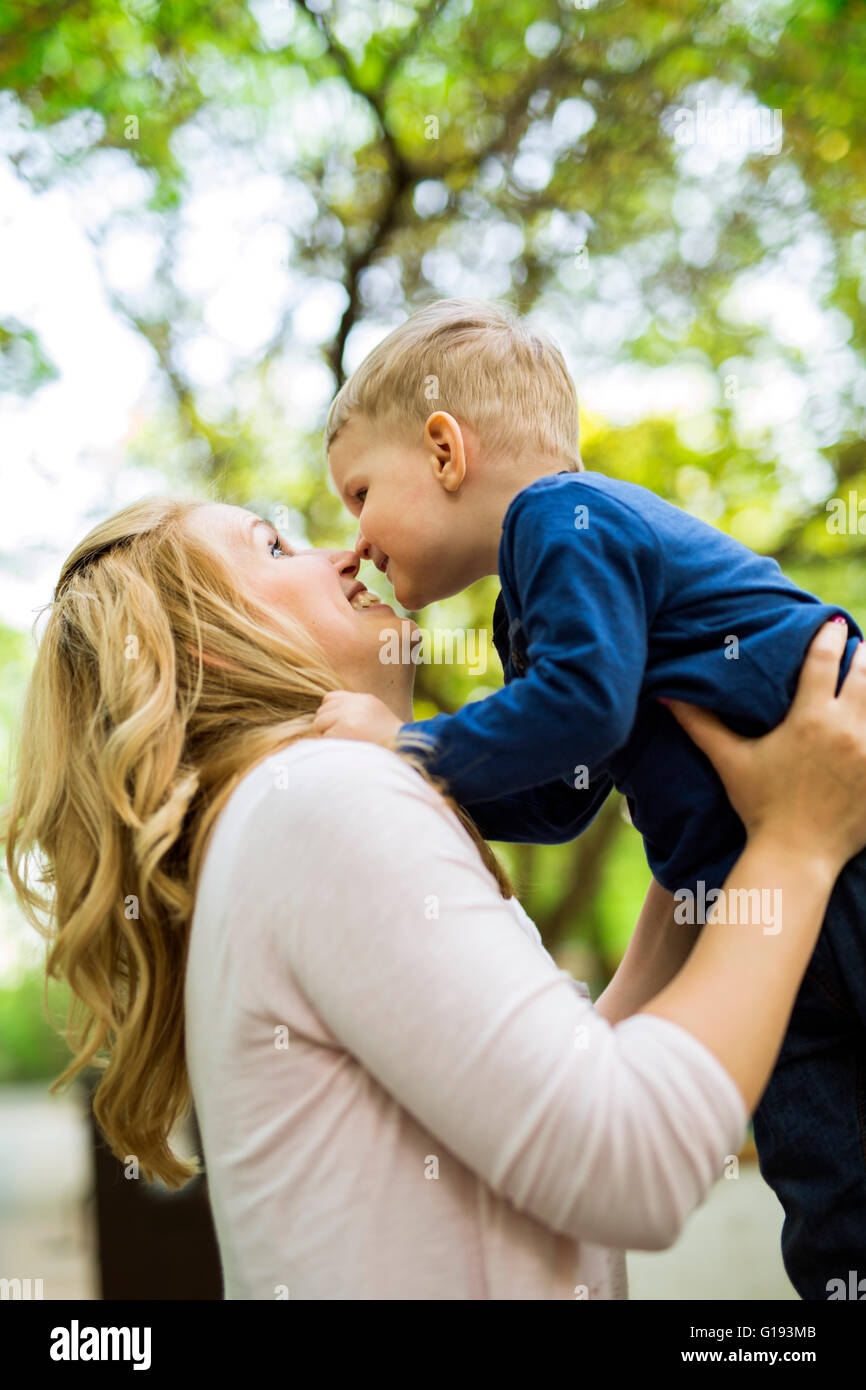 Beautiful young mother playing with her little son - Stock Image