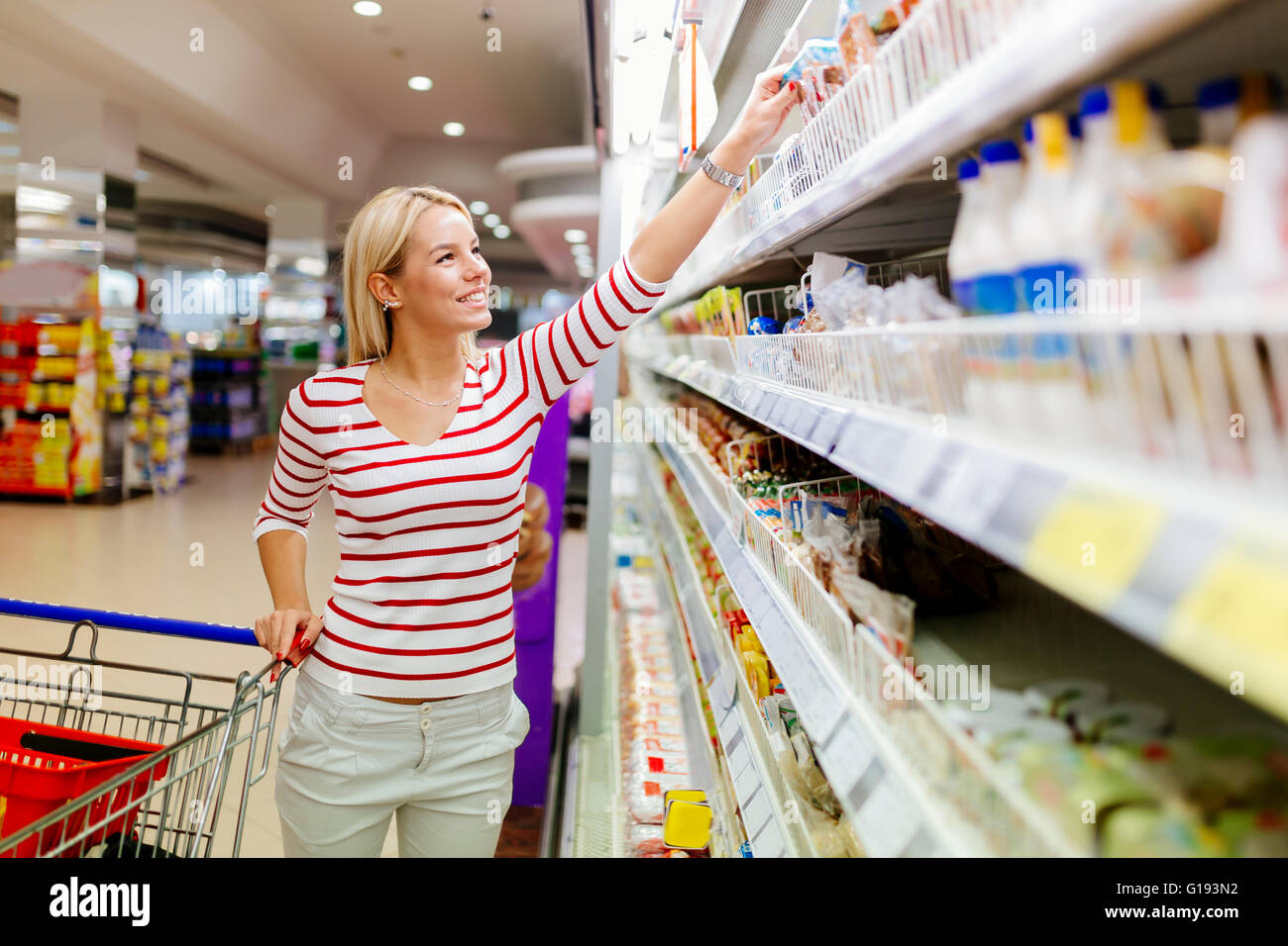 Beautiful woman shopping in supermarket and deciding what to buy - Stock Image