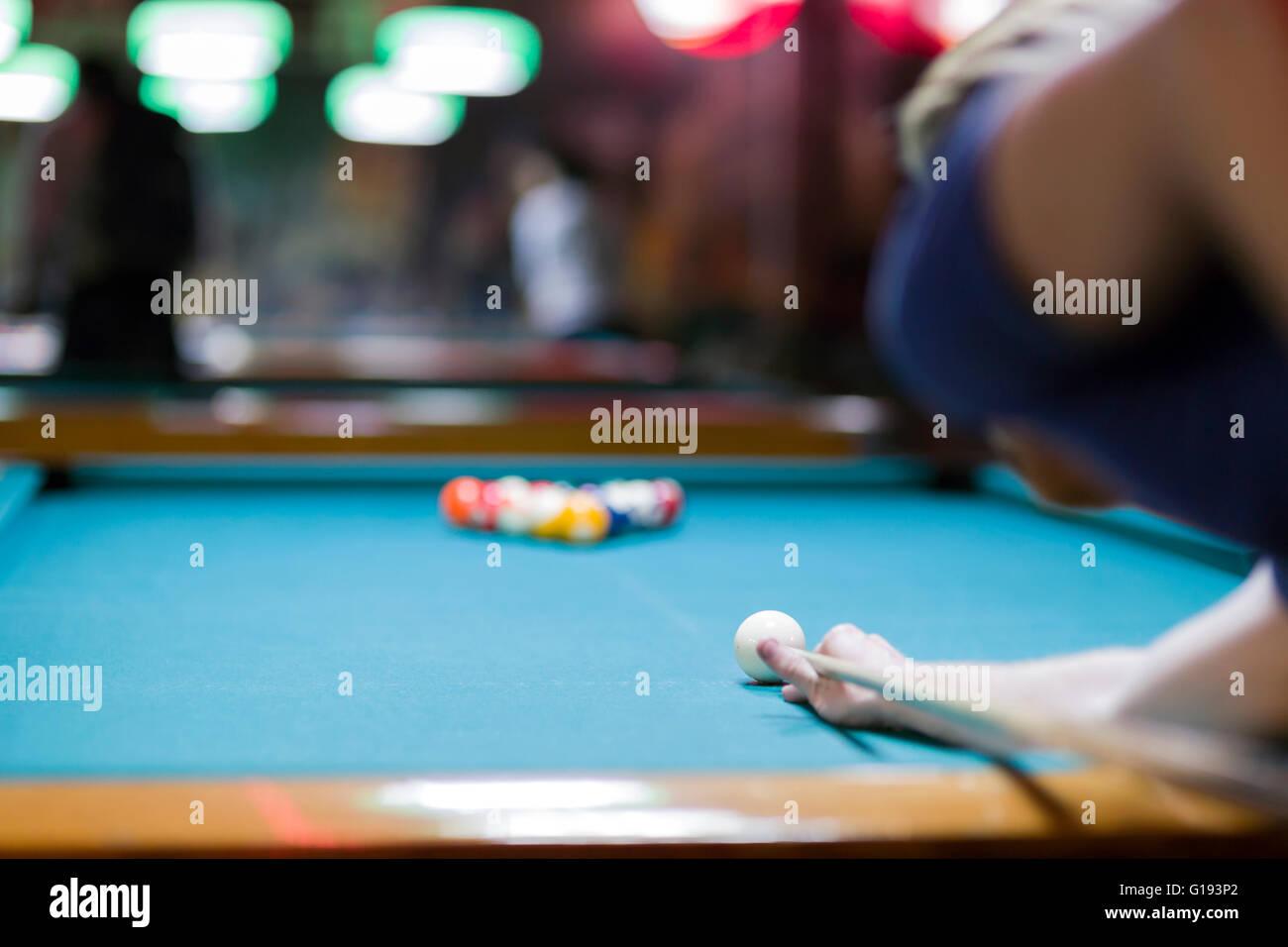 Handsome man looking to break the balls in billiard - Stock Image