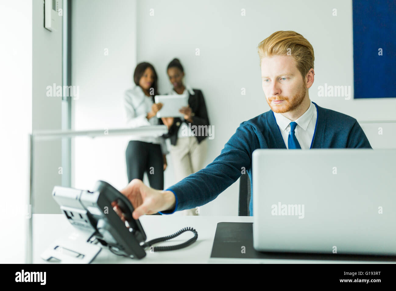Businessman about to answer the phone with two beautiful,  young women having a conversation in the background - Stock Image