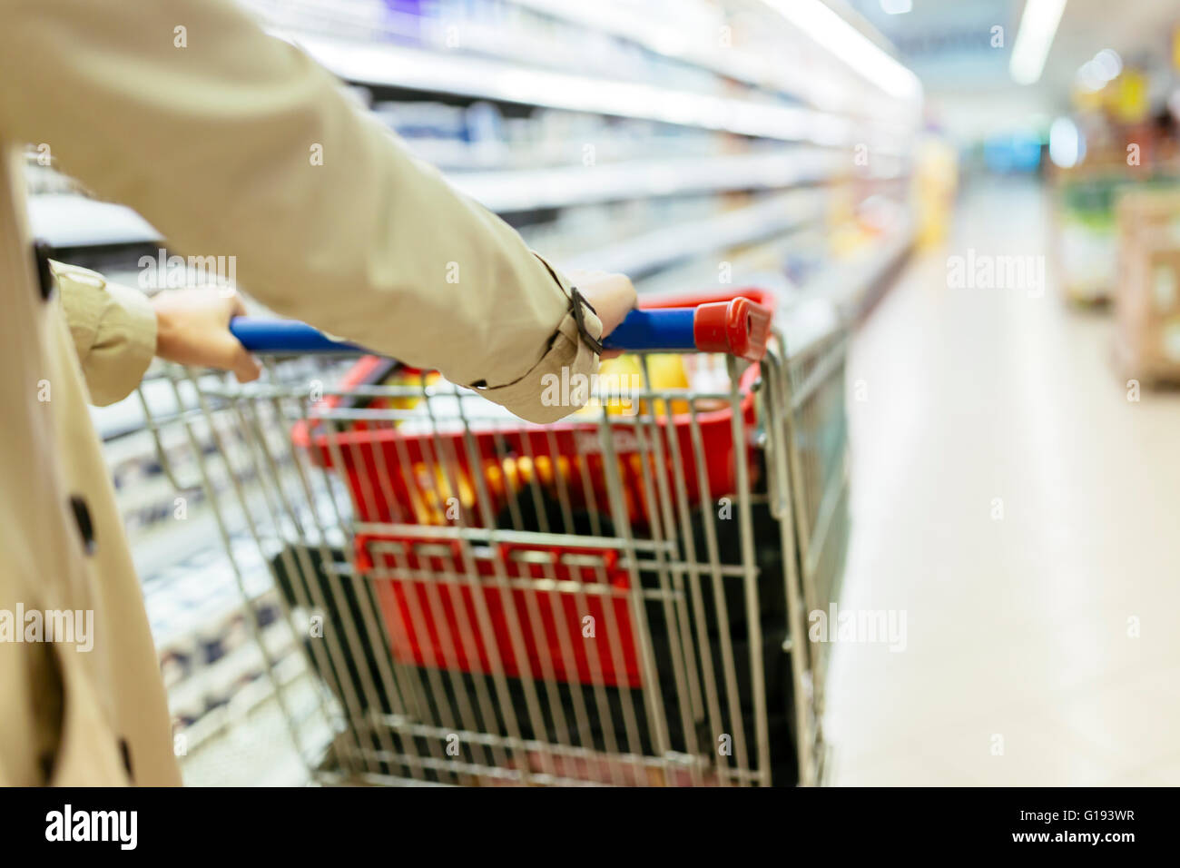 Woman pushing shopping trolley in supermarket - Stock Image