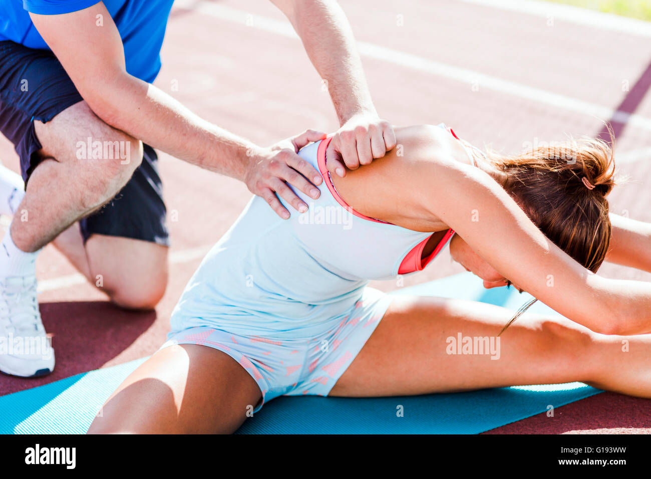 Trainer helping during strech out, outdoors shot Stock Photo