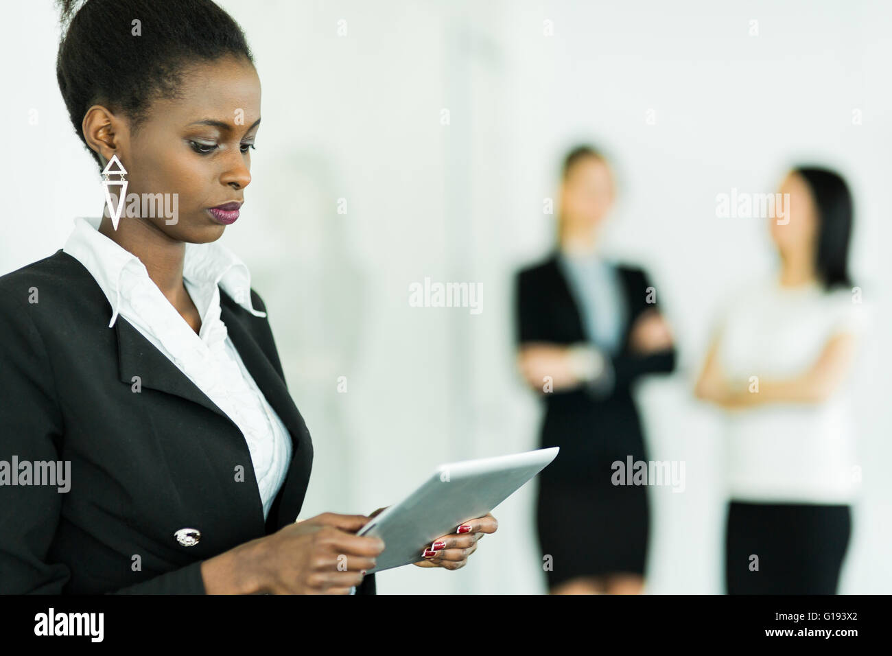 Businesswoman holding a tablet and concentrating on the contents with two colleagues blurred out in the background - Stock Image