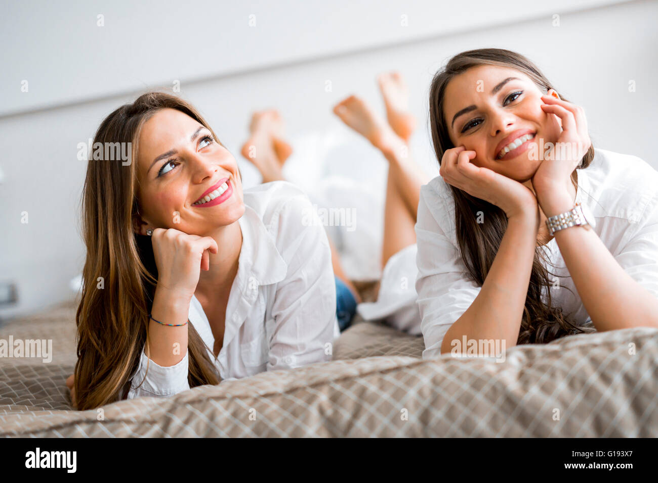 Two beautiful girls talking and smiling while lying on a luxurious  bed - Stock Image
