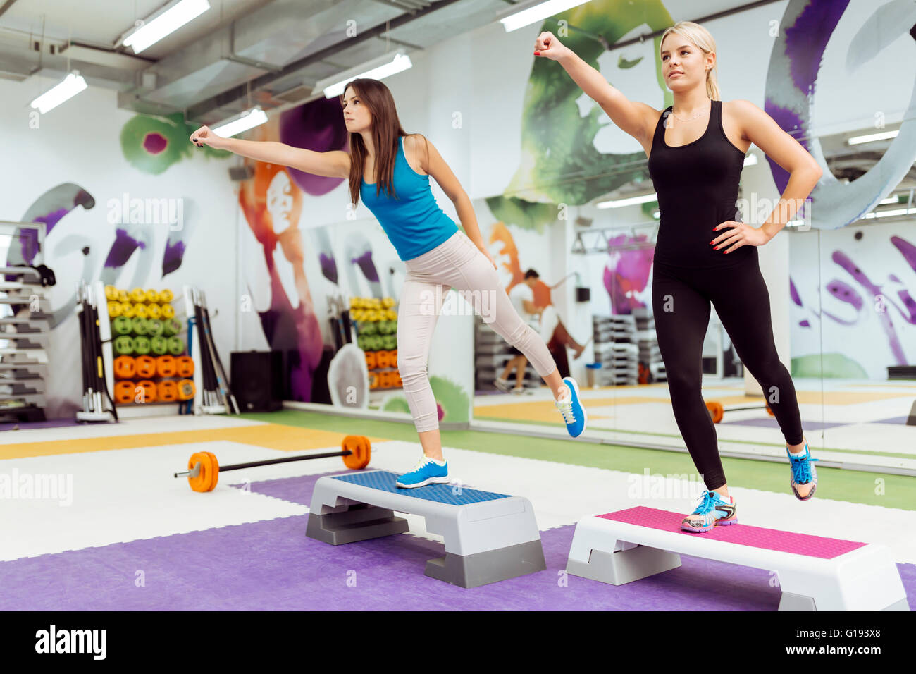 Beautiful women exercising aerobics in nice fitness club - Stock Image
