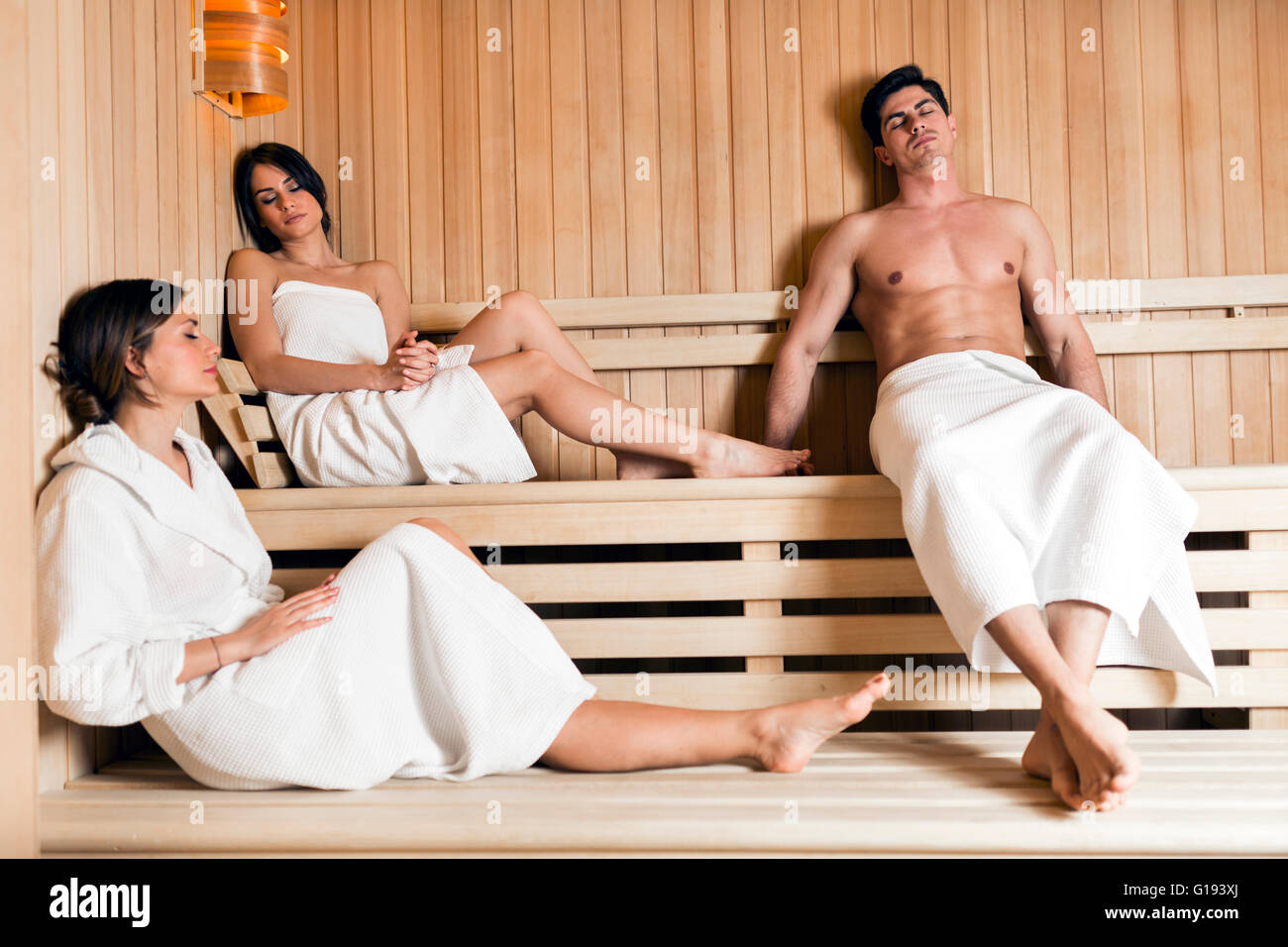 Group of young healthy, fit and beautiful people relaxing in a sauna - Stock Image
