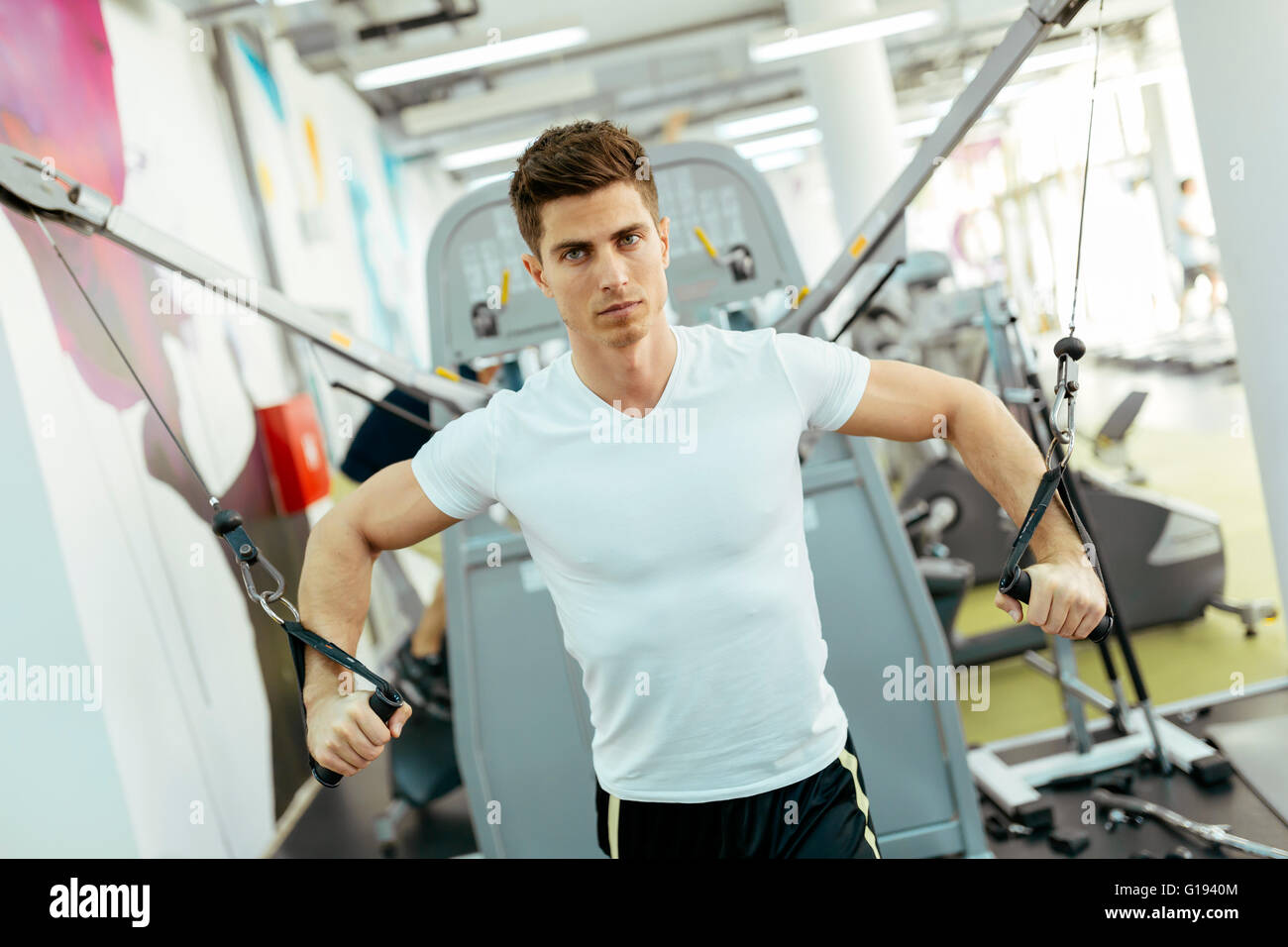 Handsome man training in clean modern gym on various machines Stock Photo