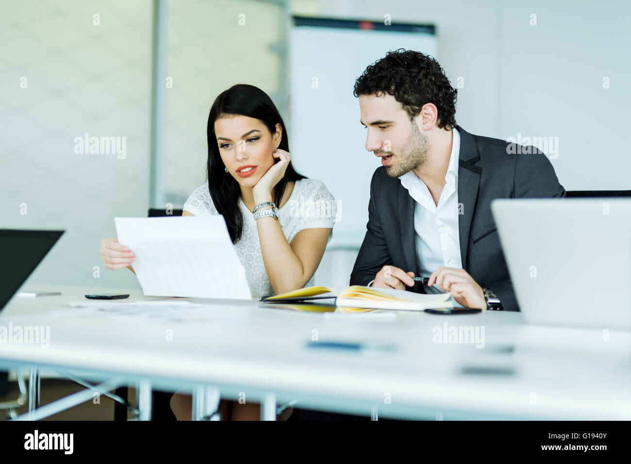 Young, successful businesswoman and a businessman looking at a paper while sitting at a office desk - Stock Image