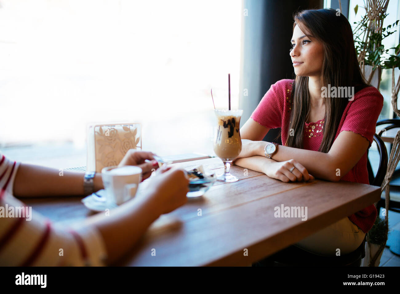 Beautiful woman talking to friend in restaurant while drinking coffee - Stock Image