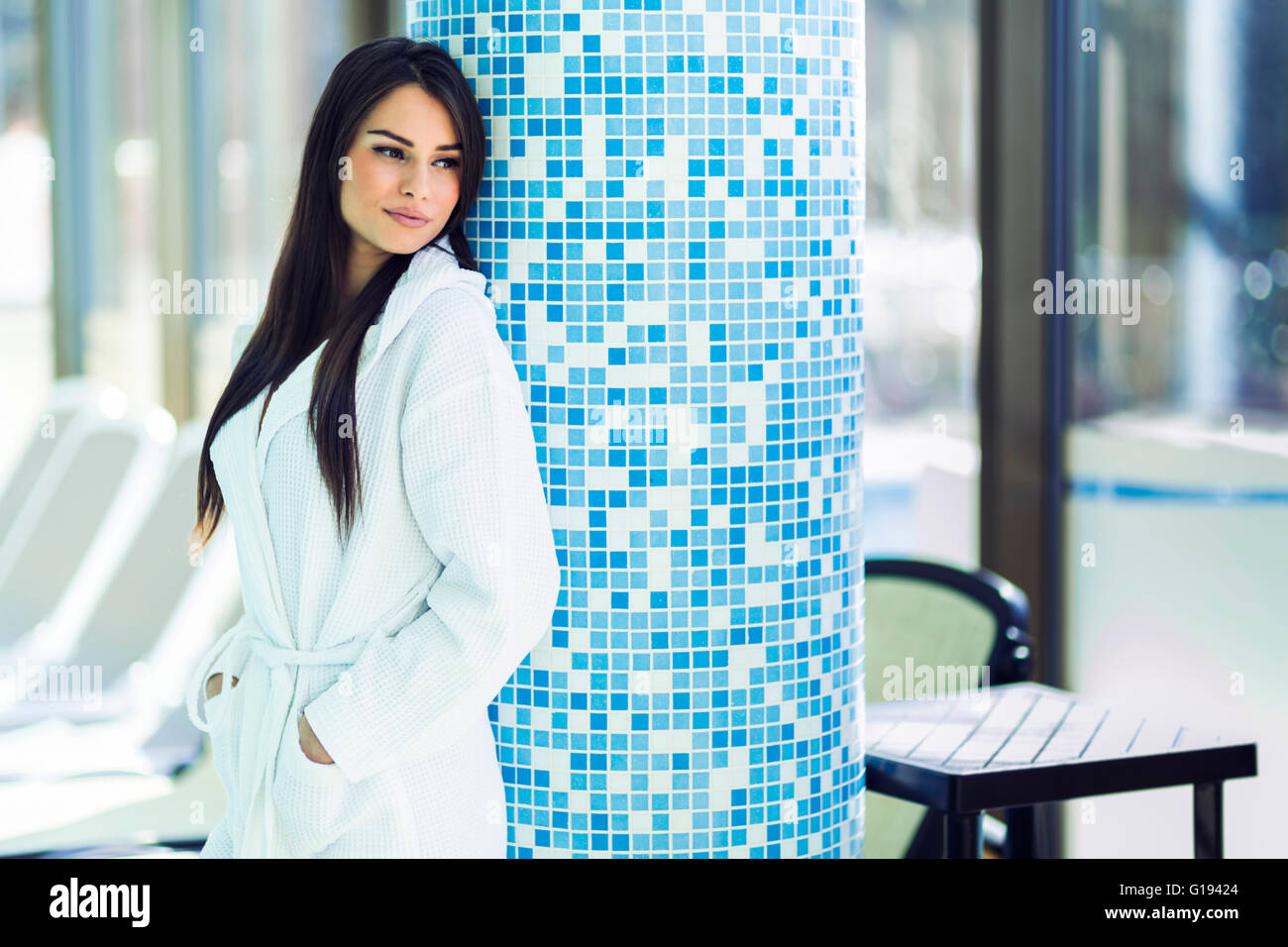 Portrait of a beautiful young woman in a bathrobe next to a swimming pool - Stock Image