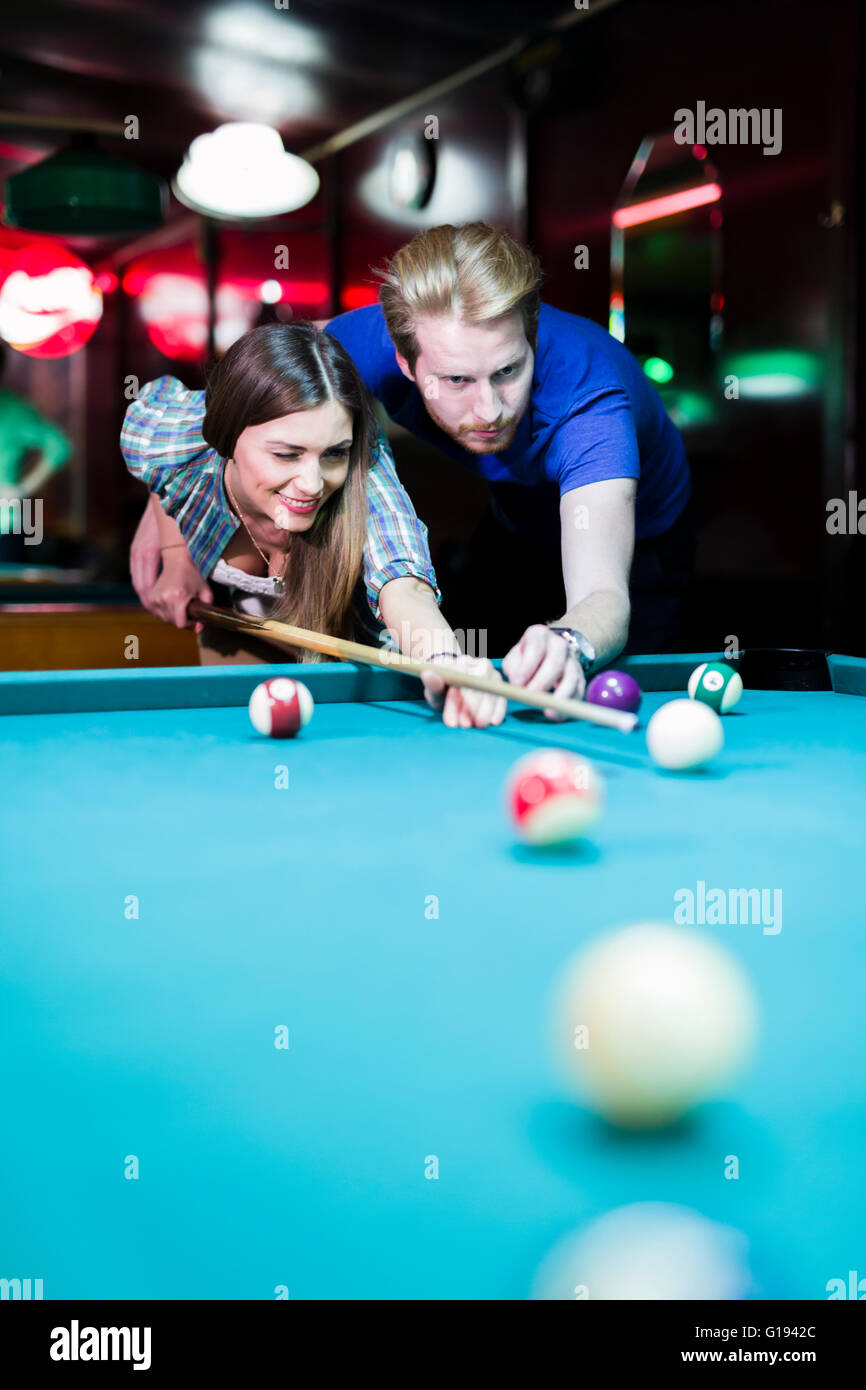 Young handsome man and woman flirting while playing billiard - Stock Image