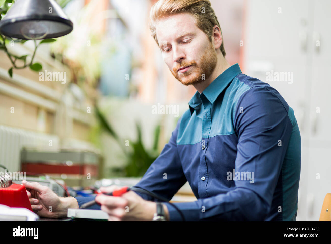 Young handsome man soldering a circuit board and working on fixing hardware - Stock Image