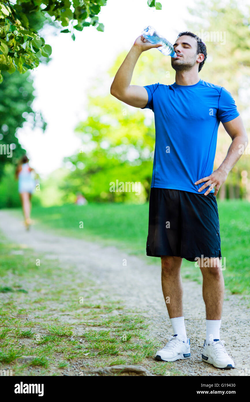 Young male athlete drinking water in the park after jogging - Stock Image