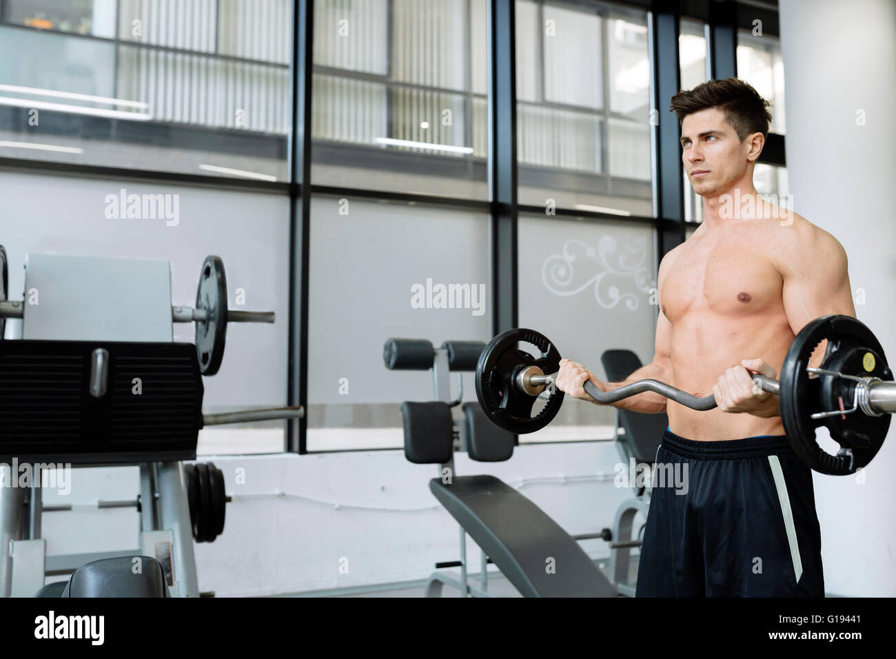 Muscular man bodybuilding in gym, lifting weights - Stock Image