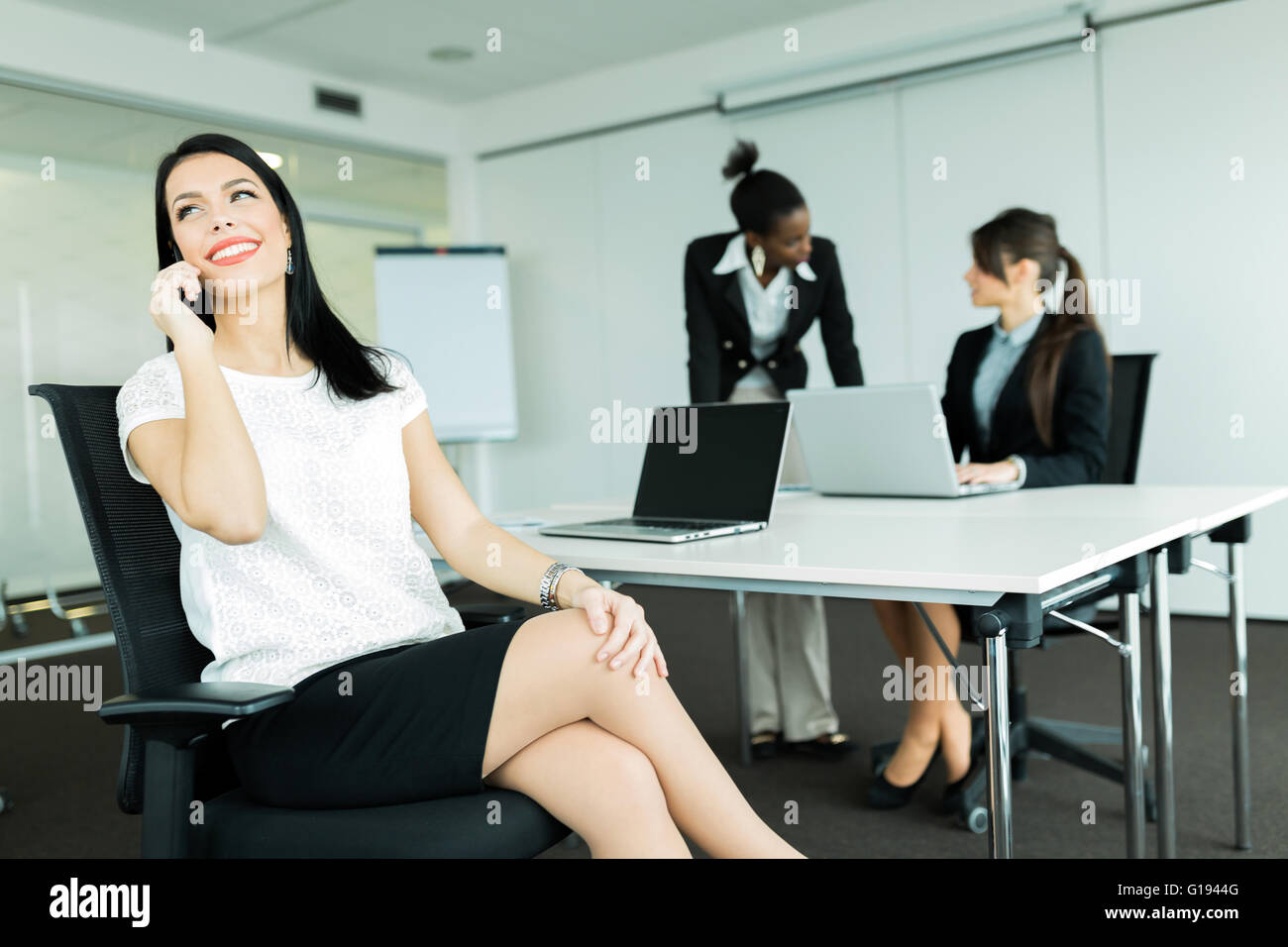 Beautiful businesswomen in an office working on a laptop and calling potential partners - Stock Image
