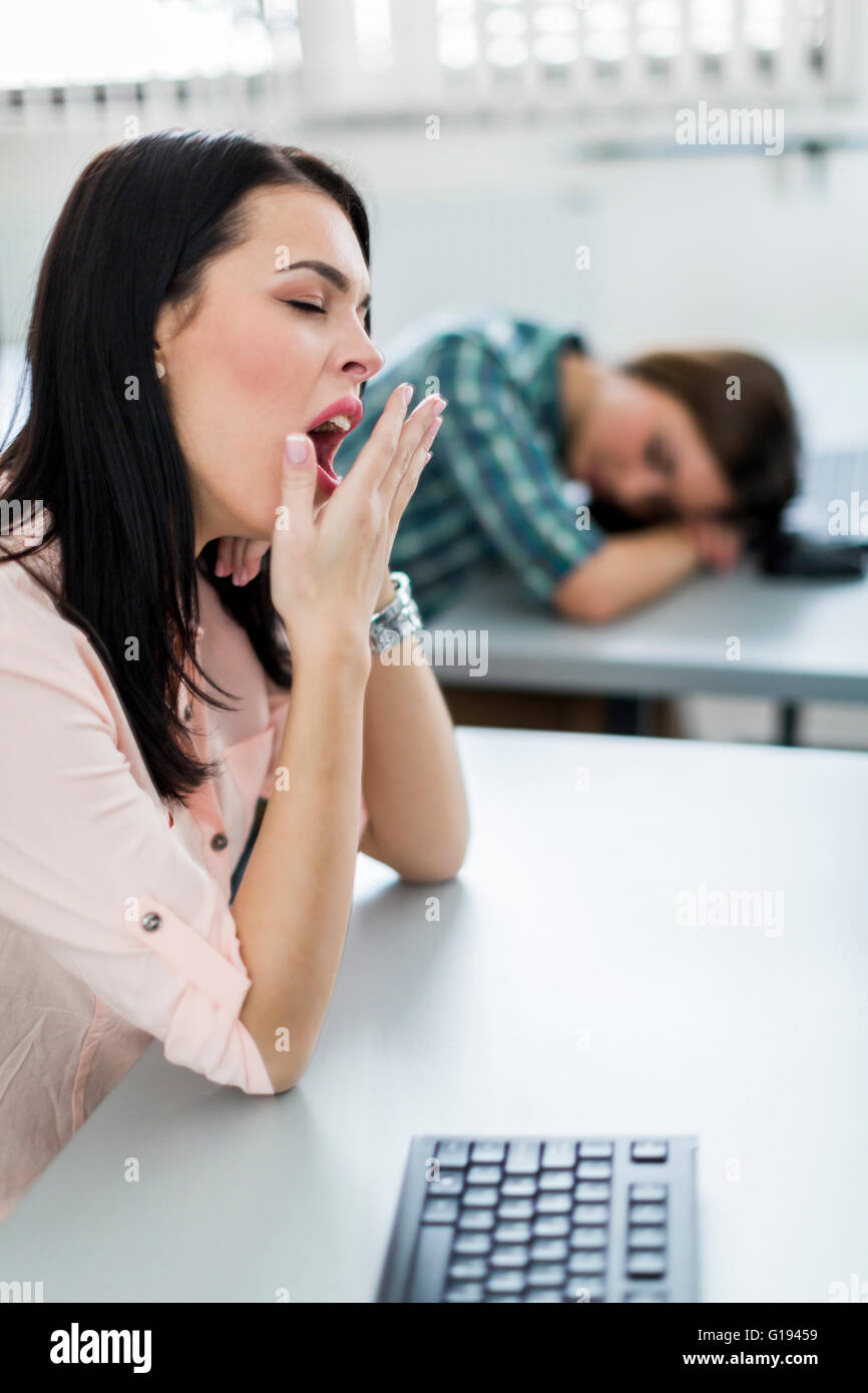 Young beautiful girl yawning during class from boredom and fatigue - Stock Image