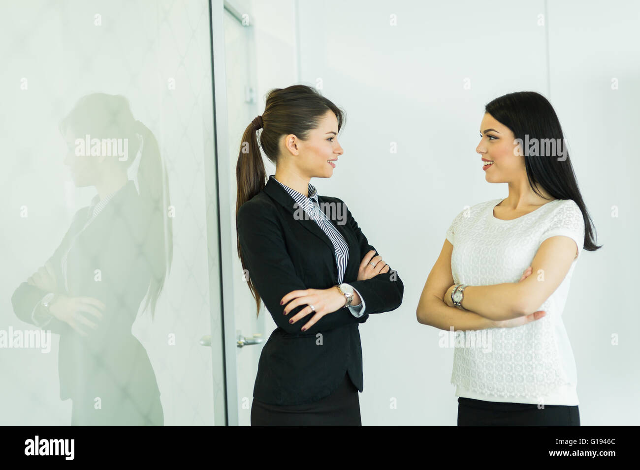 Two businesswomen talking in an office with reflection on the glass behind them - Stock Image