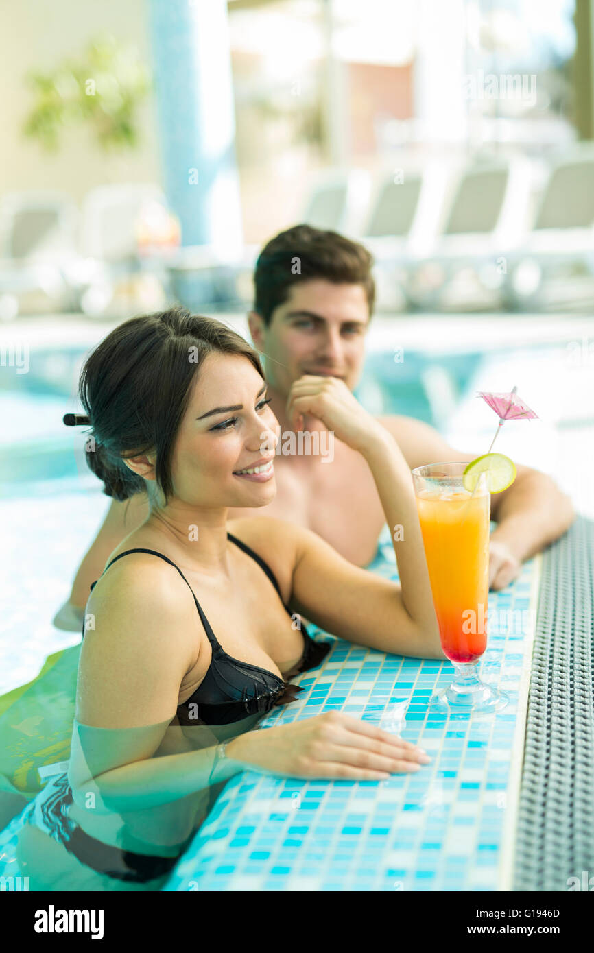 Couple drinking a cocktail by the swimming pool and relaxing Stock Photo