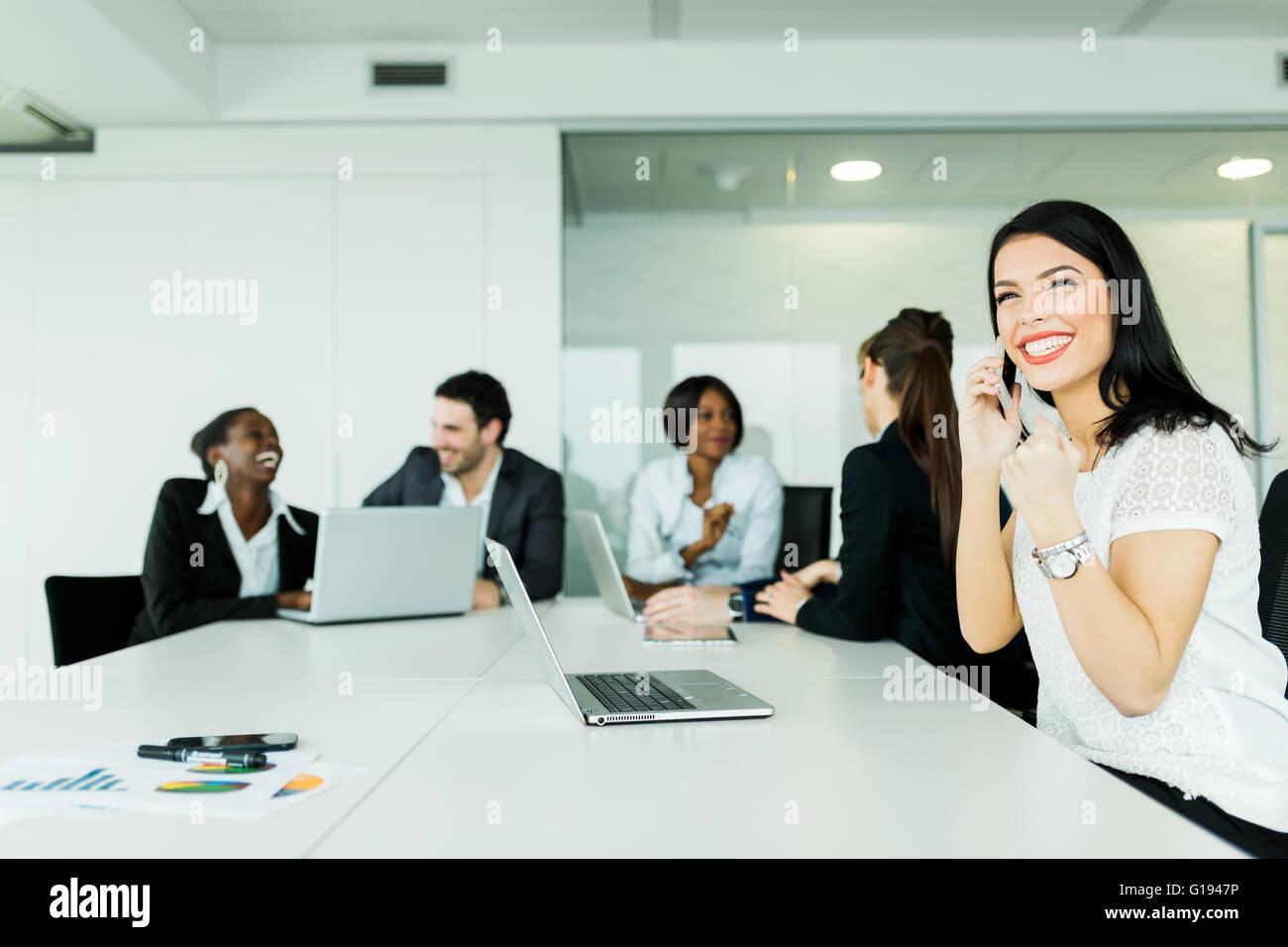 Beautiful young businesswoman receiving good news on the phone signalling success regarding future frutiful deals - Stock Image