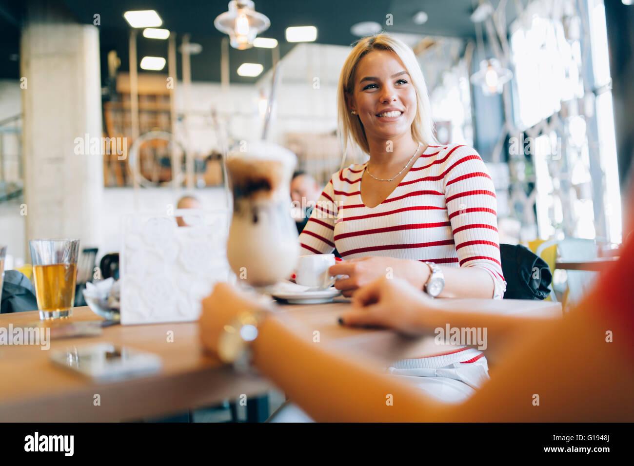 Beautiful women drinking coffee and gossiping in nice restaurant - Stock Image