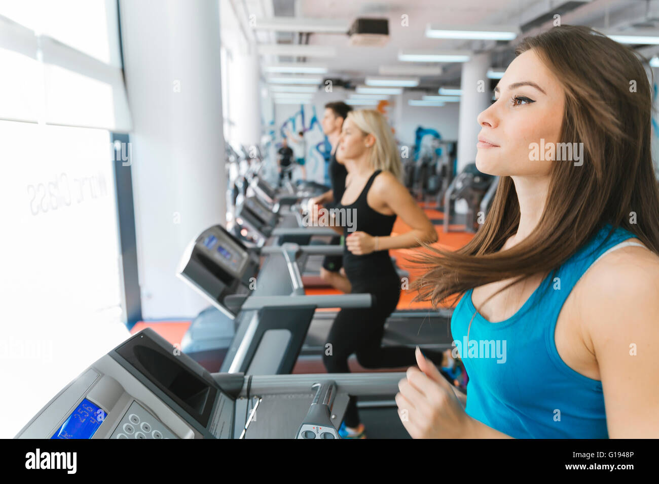 People running on treadmills in gym to keep body in shape - Stock Image